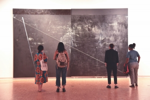 a group of students looking at a wall-sized work by dyson