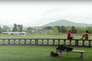 two students sitting on wall in front of expansive green misty campus and hills