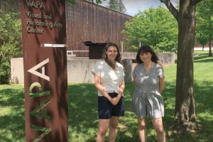 """two students in summer clothes beside metal """"VAPA"""" sign with grass, trees, and the flank of a wood-sided building"""
