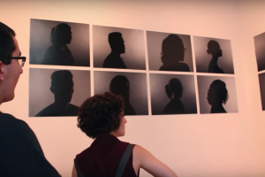 two humans in profile examine images of human profiles on a white wall