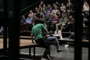 backstage view of a blackbox theatre with a full audience and two actors seated on a platform