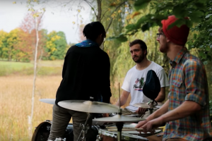 three people and two drum kits, outdoor drum class in the shade with a sunny field of high grass on the left