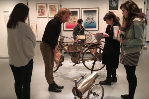 five people in a museum examining an art bike and art cannon