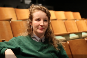 Girl in green sweater seated comfortably on well-lit wooden theatre seats