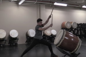 man raises arms to strike a Taiko drum in a florescent-lit windowless room with drums stacked against the cement wall