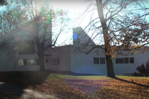sunlight streaming over Noyes House and through nearby trees
