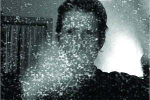grey grainy photo of man with vapors obscuring face
