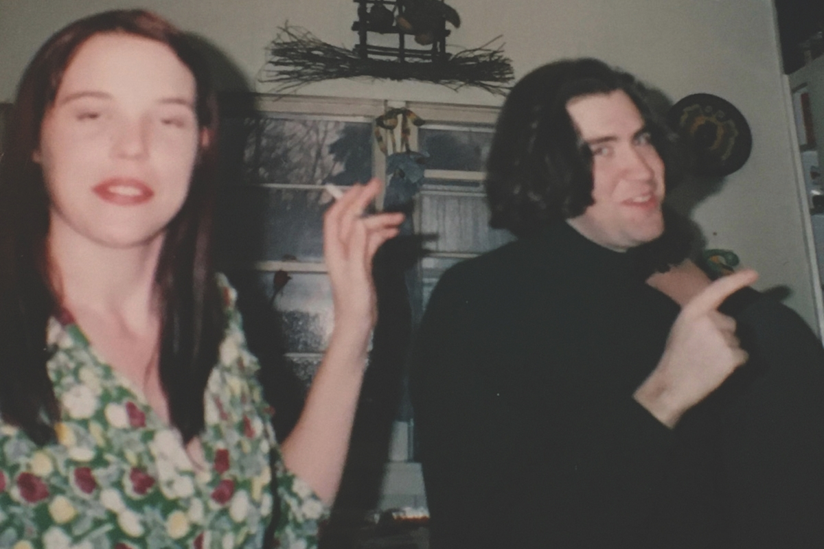 two students - a man and a woman - smile and smoke while at a party