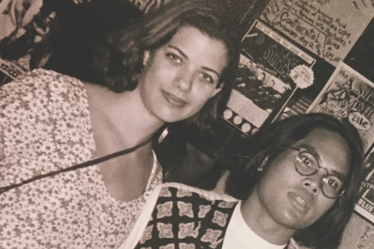 a man wearing glasses and a woman smile at the camera (sepia toned photo)