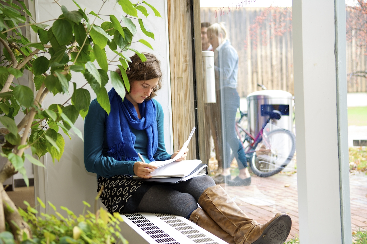 student writing in a notebook while sitting on a windowsill behind a green plant