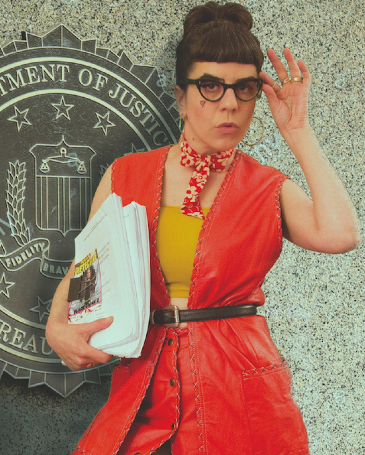 Liz, wearing a red dress, in front of the Department of Justice, holding her play