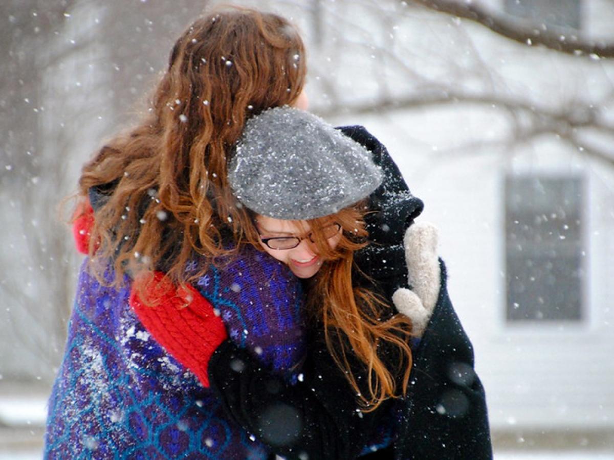 students hugging in the snow