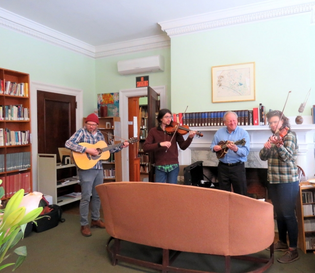 three musicians performing in the music library